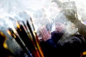 Creyentes queman incienso mientras rezan para pedir buena suerte en el templo Lama, uno de los más famosos monasterios tibetanos localizados fuera del Tíbet.