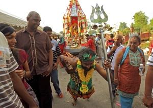 Un feligrés hinduista malasio tira de un carro con unos ganchos clavados en su espalda.