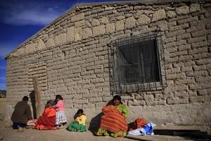 rarámuris de la comunidad de Huisarorare en la sierra tarahumara, del norteño estado de Chihuahua (México), se calientan al sol a las afueras de una de sus viviendas de estas zonas áridas del país.
