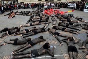BOG03. BOGOTÁ (COLOMBIA), 09/02/2012.- Unas 70 personas semidesnudas y pintadas de rojo y negro se manifiestan para reclamar el fin de las corridas de toros en el país hoy, jueves 9 de febrero de 2012, en la Plaza de Bolívar de Bogotá (Colombia). El debate antitaurino resucitó en Colombia a mediados de enero cuando arrancó la temporada de toros en una de sus plazas predilectas, la de Santamaría en Bogotá, y tuvo su germen en la decisión del nuevo alcalde capitalino, Gustavo Petro, de no ocupar el palco de la Alcaldía. EFE/Mauricio Dueñas