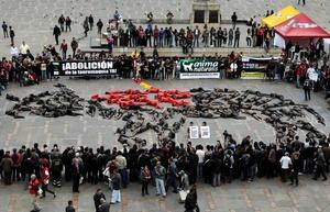BOG02. BOGOTÁ (COLOMBIA), 09/02/2012.- Unas 70 personas semidesnudas y pintadas de rojo y negro se manifiestan para reclamar el fin de las corridas de toros en el país hoy, jueves 9 de febrero de 2012, en la Plaza de Bolívar de Bogotá (Colombia). El debate antitaurino resucitó en Colombia a mediados de enero cuando arrancó la temporada de toros en una de sus plazas predilectas, la de Santamaría en Bogotá, y tuvo su germen en la decisión del nuevo alcalde capitalino, Gustavo Petro, de no ocupar el palco de la Alcaldía. EFE/Mauricio Dueñas