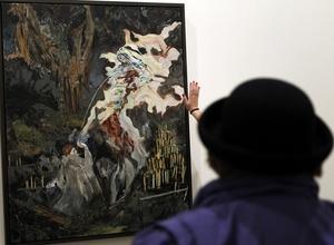Un visitante observa el cuadro del artista norteamericano Hernan Bas titulado La Inmaculada lactancia de San Bernardo.