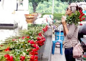 Jóvenes llevan ofrenda que exige a la diosa Trimurti ayudar a los solteros a encontrar su pareja ideal, durante la fiesta de los enamorados en Bangkok.