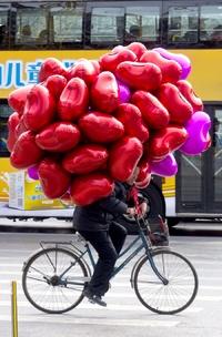 Comerciantes recorren en bici las calles de China en el Día de San Valentín.