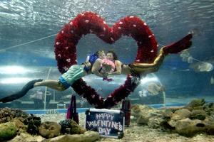 Una pareja de buzos caracterizados como Poseidon y una sirena llamada Marina, nadan cerca de un corazón que ha sido instalado en el oceanario del Manila Ocean Park para celebrar la fiesta de San Valentín.