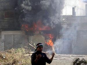 Un hombre junto a una casa en llamas bombardeada por el ejército Sirio en la ciudad de Homs.
