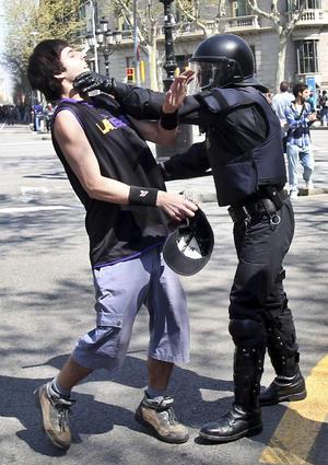 Un mosso detiene a un joven manifestante.