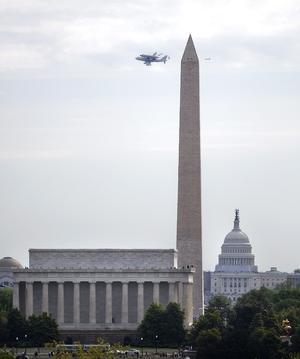 STX03 CHANTILLY (ESTADOS UNIDOS) 17/4/2012.- El transbordador Discovery sobrevuela Washington, en su último viaje antes de aterrizar en el aeropuerto internacional Dulles, en las afueras de la capital de EE.UU., y entrar a formar parte del Museo Nacional del Aire y el Espacio, hoy, martes 17 de abril de 2012. El Discovery planeó acoplado sobre el Boeing 747 modificado de la NASA durante unos 40 minutos sobre la capital estadounidense y sus principales monumentos y edificios. Numerosas personas se lanzaron a las terrazas y a las calles para ver el transbordador que batió el récord de viajes al espacio. EFE/SHAWN THEW