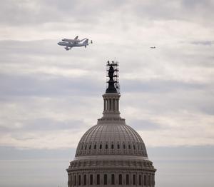 WAS01 WASHINGTON (ESTADOS UNIDOS) 17/4/2012.- El transbordador Discovery sobrevuela Washington, en su último viaje antes de aterrizar en el aeropuerto internacional Dulles, en las afueras de la capital de EE.UU., y entrar a formar parte del Museo Nacional del Aire y el Espacio, hoy, martes 17 de abril de 2012. El Discovery planeó acoplado sobre el Boeing 747 modificado de la NASA durante unos 40 minutos sobre la capital estadounidense y sus principales monumentos y edificios. Numerosas personas se lanzaron a las terrazas y a las calles para ver el transbordador que batió el récord de viajes al espacio. EFE/NASA/Smithsonian Institution/Harold Dorwin) OBLIGATORIO CITAR FUENTE