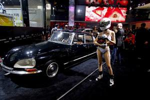 Una modelo posa en bikini y con un casco cubriendo su cabeza al lado de un Citröen DS de época en el Salón del Automóvil de China.