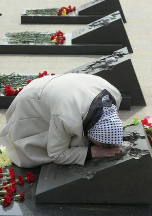 Una mujer ucraniana llora sobre la tumba de su hijo, un bombero que acudió a la central de Chernóbil y murió poco después de la tragedia nuclear, en un cementerio en Moscú, Rusia.