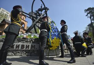 Unos miembros de una guardia de honor hacen una ofrenda floral durante una ceremonia en memoria de las víctimas de la catástrofe nuclear de Chernóbil en Kiev, Ucrania.