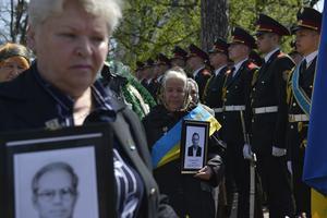 Unas mujeres sostienen fotografías de sus seres queridos durante la ceremonia del 26 aniversario del accidente.
