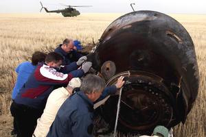 Personal de la agencia espacial rusa mueven la cápsula Soyuz TMA-22 justo después de aterrizar en Kazajistán. (EFE)