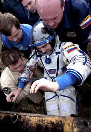 El astronauta ruso Anatoly Ivanishin es ayudado a salir del módulo de descenso de la nave rusa. (EFE)