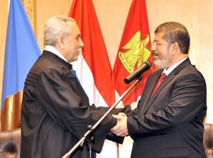 Vestido con traje azul oscuro y corbata roja, Mursi leyó el juramento de un papel ante el pleno, presidido por el juez Faruq Sultan, que encabeza también la Comisión Electoral Presidencial.