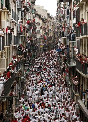 """Cientos de """"mozos"""" corren por las estrechas calles del casco histórico de la ciudad delante de seis toros en un tramo de unos 800 metros, los que separan los corrales de Santo Domingo del coso taurino."""