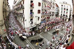 Pamplona celebra sus fiestas de San Fermín con los tradicionales encierros donde los mozos corren por delante de los toros hasta la plaza taurina además de eventos culturales.