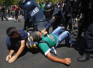 Poco después de la llegada del grueso de la manifestación, los manifestantes comenzaron a empujar la valla metálica, que lograron volcar, y provocaron con los lanzamientos de petardos y piedras que los agentes tuviesen que protegerse con sus escudos.