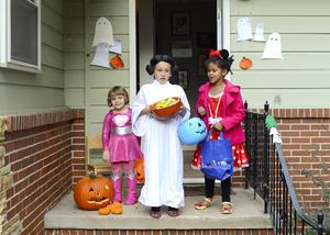 En sus hogares, niños disfrazados esperaban entregar dulces a quienes tocaban sus puertas.