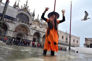 Jóvenes salieron a la inundada plaza de San Marco en Venecia con sus disfraces de Halloween.