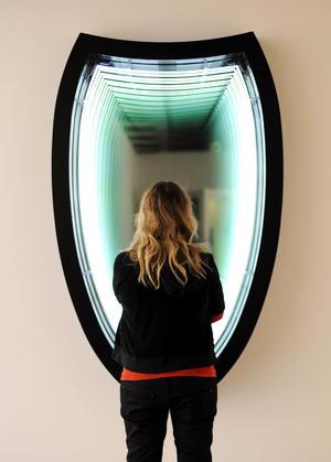 """Entre la veintena de artistas presentes se encuentra el chileno Iván Navarro, con sus obras """"Burden (Lotte World Tower)"""" (2010) y """"Reality Show"""" (2011), un cubículo en forma de cabina telefónica que se refleja a sí mismo hasta el infinito y en el que el observador parece desaparecer."""