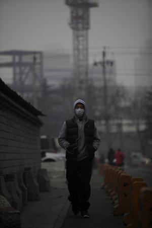 Un viandante utiliza una mascarilla mientras camina por una calle de Pekín (China). Los pekineses urgieron al gobierno a poner freno a la contaminación tras declararse ayer la alarma por la nube de contaminación que envuelve la ciudad.