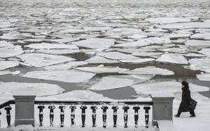 Una mujer camina por delante del hielo que flota sobre el río De Moscova en Moscú.