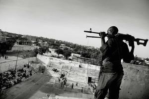 """Imagen del fotógrafo danés Jan Grarup tomada el 21 de febrero de 2012 en Mogadiscio (Somalia) y que forma parte de la serie """"Solo quiero hacer mates"""" ganadora del primer premio en la categoría """"Noticias Deportivas"""".  En la imagen aparece uno de los guardias pagados por la Federación Femenina de Baloncesto somalí para que protejan a las jugadoras durante un partido en Mogadiscio."""
