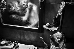 """Imagen tomada en Roma (Italia) por el fotógrafo italiano Fausto Podavini que forma parte de su serie """"Mirella"""" y que ha ganado el primer premio en la categoría de """"Historias de la vida cotidiana"""".   En la imagen se muestra a Mirella mientras cuida de su marido Luigi, enfermo de Alzheimer, en Roma (Italia) el 1 de junio de 2010. Mirella dedica su vida a cuidar de su marido e intenta ser positiva encargándose de él con mucho amor y respeto. El cuidado diario que normalmente lleva minutos en su caso requiere horas debido a la demencia de su marido. Mirella, de 71 años, ha pasado 43 años de su existencia con el amor de su vida. Pero los últimos seis años las cosas cambiaron debido a la enfermedad de Luigi."""