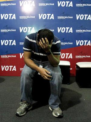 Un seguidor del candidato presidencial venezolano Henrique Capriles Radonsky se lamenta, tras conocerse la victoria de Nicolás Maduro, en la sede del comando de campaña de Capriles, en Caracas.