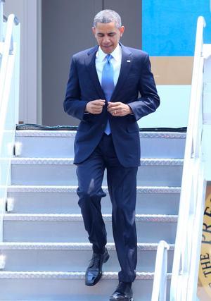 El jefe de Estado llegó vestido con un traje negro, camisa blanca y corbata tono gris; acompañado por asesores y funcionarios de su gobierno, bajó rápidamente la escalinata y de buen humor saludó con la mano derecha a quienes acudieron a recibirlo.