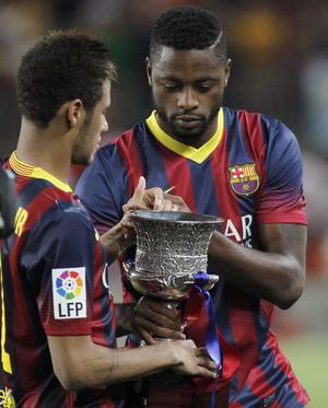 Alex Song contempla el trofeo de la Supercopa con su compañero Neymar.