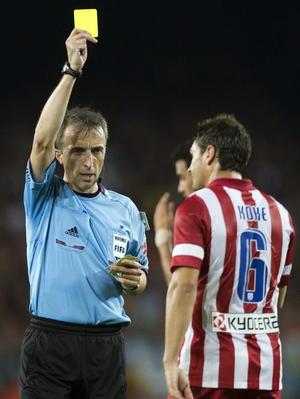 Koke recibiendo tarjeta amarilla por cometer una falta a Messi.