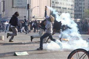 """Los enfrentamientos se dieron en varios puntos de la trayectoria seguida por estudiantes, activistas y organizaciones sindicales cuando los """"anarquistas"""", muchos de ellos con los rostros cubiertos, arrojaron botellas, piedras y otros objetos contra los agentes, que respondieron con gases lacrimógenos, según se constató."""