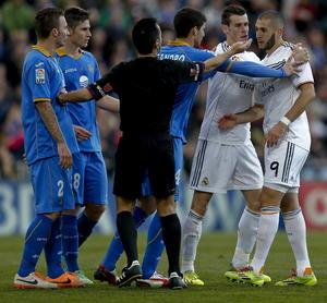 Gareth Bale separa a su compañero Karim Benzema al enfrentar al jugador Alexis Ruanoz del Getafe.