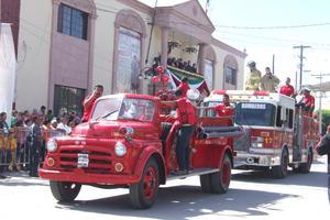 Apagafuegos. La vieja máquina apagafuegos, fue parte del desfile. A bordo los elementos del Heroico cuerpo de Bomberos.