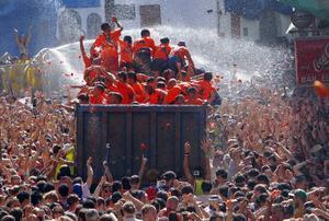 En la fiesta anual en Buñol, a unos 50 kilómetros de Valencia, los camiones descargaron 125 toneladas de tomates maduros para diversión de unos 22,000 participantes, muchos de ellos extranjeros.