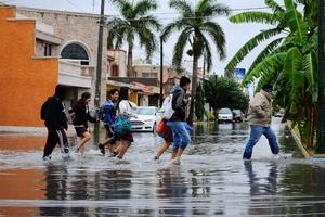Los peatones se sortean al cruzar las calles con inundaciones para llegar a su destino.