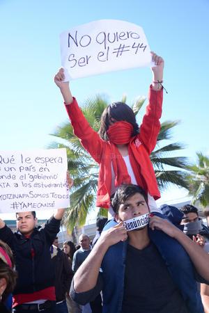 """Los manifestantes exigieron justicia y solución en el caso de los normalistas desaparecidos de Ayotzinapa, portando carteles señalando que ellos no querían ser """"el 44""""."""