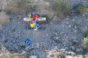 A un lado del camino de terracería se puede apreciar una cruz de un accidente.