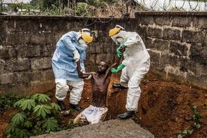 Pete Mulle captó a personal sanitario de un centro de atención a enfermos de ébola mientras ayudan a un enfermo en estado de delirio.