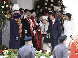 Vestida con un abrigo de color marfil con detalles verde oliva y un sombrero de Angela Kelly, Isabel II, de 88 años, intercambió palabras con el presidente y después le presentó a los miembros del Ejecutivo.