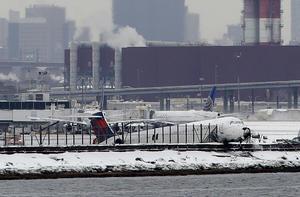 Los equipos de urgencias evaluaban a la gente que debió abandonar el avión y se vio a una persona subiendo a una ambulancia en el aeropuerto.