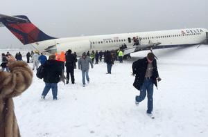 Los pasajeros abandonaron el avión deslizándose por una rampa inflable hacia el pavimento cubierto de nieve.