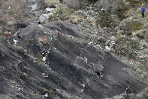 Miembros de los servicios de rescate colocan marcas rojas para realizar su trabajo entre fragmentos del avión esparcidos por un área de alta montaña.