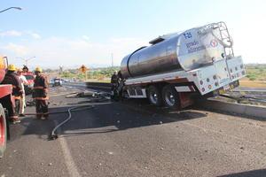 El camión se impactó contra la base de concreto de un anuncio carretero que derribó y posteriormente se proyectó contra la barrera de contención, donde quedó colgando.