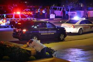 Un hombre cae devastado ante la brutal escena donde fueron asesinadas nueve personas.