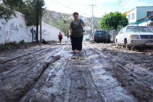 Los habitantes tienen que caminar entre el lodo.
