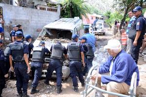 Vehículos que estaban estacionados a un lado del arroyo que se desbordó al caerle una gran cantidad de lluvia del cerro, resultaron con graves daños.